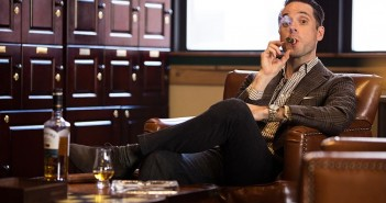 holding-cigar-in-mouth-sitting-in-cigar-lounge-leather-chair-drinking-scotch